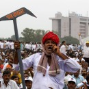 A member of the Patel community holding a mock plow shouts slogans during a protest rally in Ahmedabad, India, Aug. 25