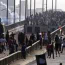 Members of the Muslim Brotherhood and supporters of ousted Egyptian President Mohammed Morsi flee from tear gas and rubber bullets fired by riot police during clashes on a bridge leading to Rabaa al-Adwiya Square in Cairo on August 14, 2013