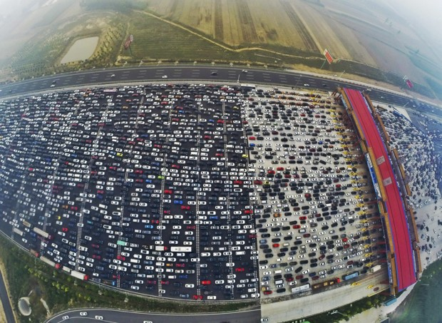 Vehicles are seen stuck in a traffic jam near a toll station as people return home at the end of a week-long national day holiday, in Beijing, China, October 6, 2015. Picture taken October 6, 2015. REUTERS/China Daily CHINA OUT. NO COMMERCIAL OR EDITORIAL SALES IN CHINA     - RTS3HL5